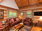 The living room has leather sofas and hand-made tables, custom drapes, and hardwood floors.