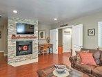 The beautiful home has a stone fireplace, plush furniture, & a flat-screen TV.