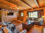 The home's spacious interior is outfitted with wood paneling and mountain decor.
