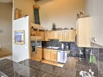 The fully equipped kitchen provides modern stainless steel appliances, including a gas-burning stovetop.