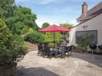 A large patio area at the back of the house with 2 charcoal barbecues and plenty of seating