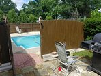 Backyard pool with privacy fence and three grills