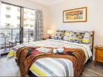 A bright and airy bedroom with a balcony that overlooks the tennis court