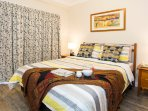 A comfortable queen-size bed for a relaxed slumber with blocked-out curtains