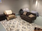 Basement with seating area and queen bed