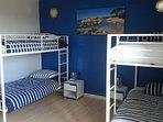 Chambre bleue avec 4 lits de 90x200 située au rdc