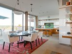 Look south to the open plan dining area and kitchen that opens onto the deck and BBQ grill.