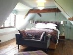 The top bedroom with kingsize bed and views over the garden and fields