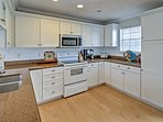 The kitchen comes complete with stainless steel appliances, bright white cabinetry and plenty of counter space.