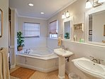 This private en suite bathroom boasts double sinks, a jetted tub and a walk-in shower.