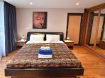King bed, mirrored teak wardrobe cupboards, bright night lights for reading