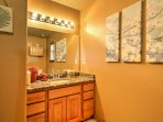 The bathroom features a brightly lit and spacious sink space.