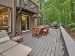 The backyard is surrounded by woods and offers a quiet escape, complete with a fire pit and hammock.