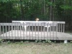 Large wooden deck with table and chairs for use in common area.