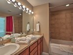 The master bedroom boasts a full en suite bathroom equipped with a tub-shower combo and double vanity.