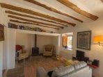 De sfeervolle en authentieke woonkamer met houtkachel in de brede schouw