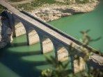 De oude brug in Iznajar over het blauwgroene meer