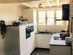 full kitchen with eye level oven, microwave, full size dishwasher, fridge freezer & washing machine.