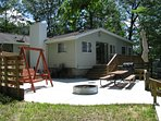 Patio area, fire ring, swing, picnic table, grill, canopy, deck.