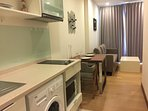 Living area in the room with washing mechine and kitchen wears