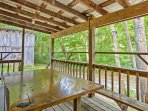 The covered porch of this 4-bedroom, 3-bathroom vacation rental cabin in Taswell looks out upon Hoosier National Forest.