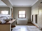 Bedroom 1 has an unsuite bathroom with a double shower or freestanding stone bath to soak in after a