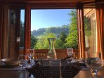The dining table looks onto the balcony and mountain views
