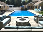 View of the patio with comfortable seating around the gas firepit, outdoor kitchen and bar all around the beautiful...