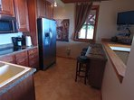 2nd floor kitchen with bar seating.  27 inch flat screen TV and picture window face the lake.