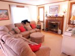 main living room with fireplace, nice wrap-around sofa to relax watch TV on large flat panel TV