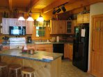 Fully equipped kitchen with pots, pans, dishes, glasses, utensils, and much more