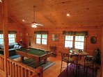 Loft with pool table, saloon style table and chairs, sleeper sofa, and game collection