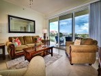 Living room has plenty of comfy seating and access to the balcony.