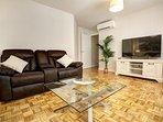Salón con sofás comodísimos reclinables y Smart TV de 55 pulgadas.