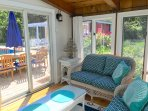 Bright sun room off the family room, perfect place to relax with a book in a sunny, screened room