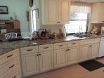 remodeled kitchen with easy close drawers and cabinets and new tile floor.