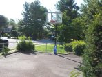 Asphalt paved basketball court for exercise surround by chain link fence.