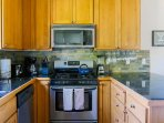 The modern kitchen is equipped with a gas stovetop and stainless steel appliances