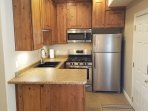Kitchen includes fridge, freezer, stove, and microwave.