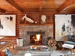 The cozy living room boasts a beautiful stone wood-burning fireplace.