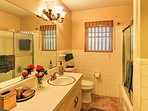 This en suite bathroom features a tub-shower combo and spacious vanity.