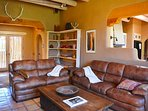 French door foyer, comfy leather sofas and view to open kitchen.