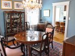 A chandelier and exquisite dining room table invites formal family dinner.