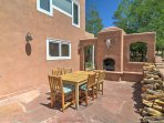 The outdoor kiva fireplace provides a stunning backdrop during a family feast.