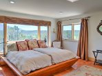 The custom cherry wood bed is set against triple-pane windows with breathtaking views of the Sangre de Cristos...