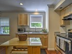The kitchen features stainless steel appliances and a quaint center island.