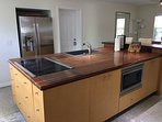 Modern fully equipped double-island kitchen with walnut butcher block top