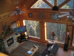 The cabin's main level features open design, large windows, and cathedral ceilings.