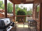 Porch outside of lower floor with grill and view of outdoor pool in the background