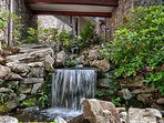 A stream and waterfall feature running under the house